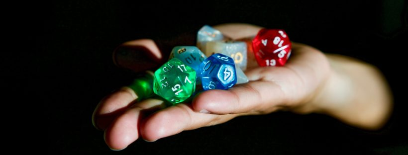 Reaching out from the shadows, a hand holds a collection of multicolored, polyhedral dice.