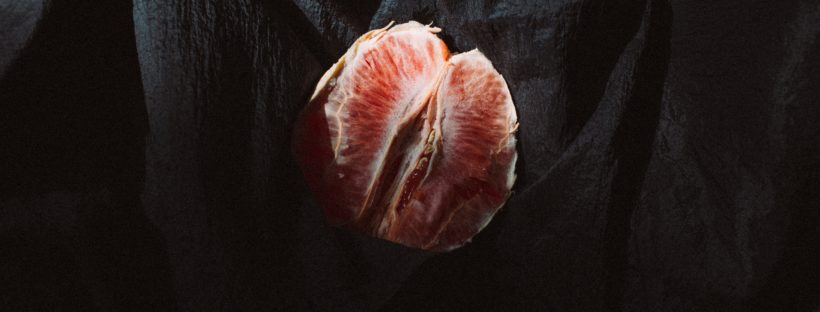 A blood orange, peeled and halved, lies partially covered on a wrinkled, black sheet.